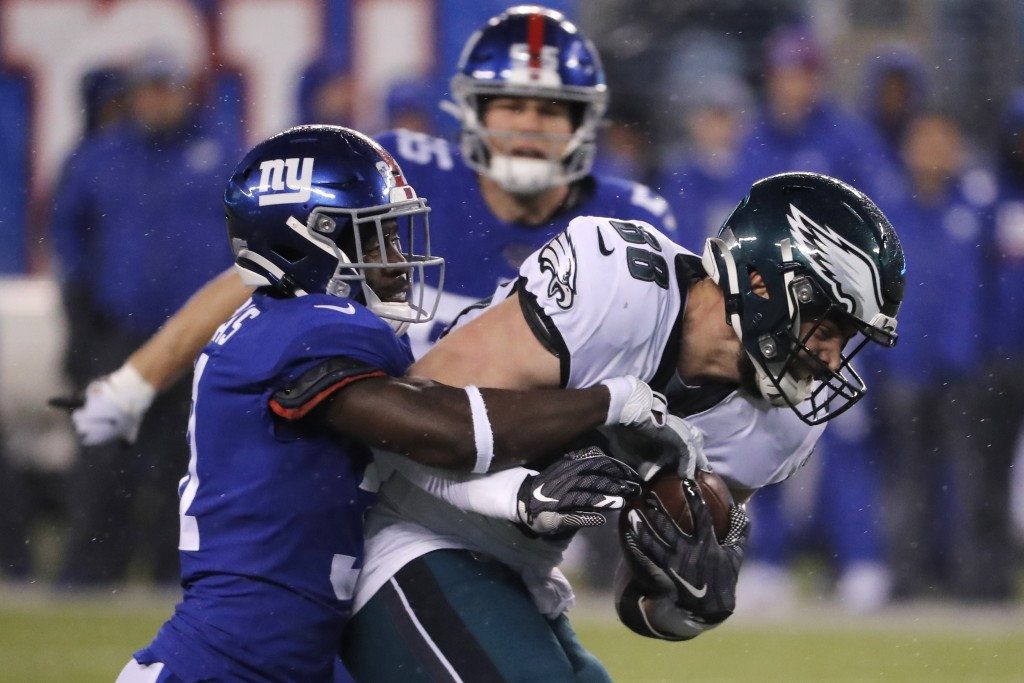 Philadelphia Eagles tight end Dallas Goedert (88) is stopped after a catch by New York Giants defensive back Michael Thomas (31) NFL football game, Su...