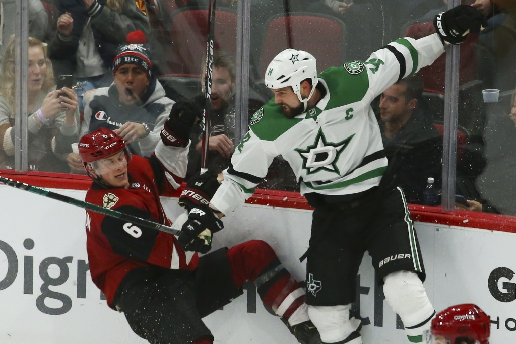 Dallas Stars left wing Jamie Benn, right, checks Arizona Coyotes defenseman Jakob Chychrun (6) to the ice during the second period of an NHL hockey ga...
