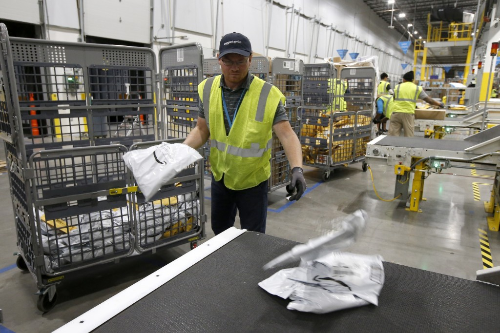 In this Dec. 17, 2019, photo Steven Smith places packages onto a conveyor prior to Amazon robots transporting packages to chutes that are organized by...