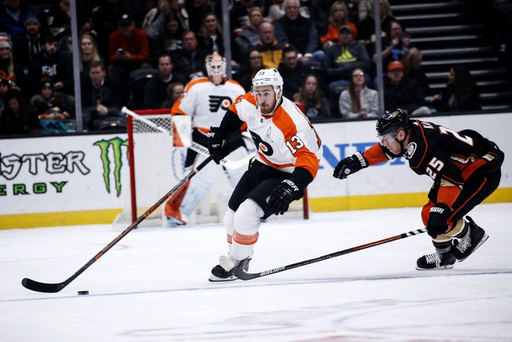 Philadelphia Flyers forward Kevin Hayes (13) keeps the puck away from Anaheim Ducks forward Ondrej Kase (25) during the first period of an NHL hockey ...