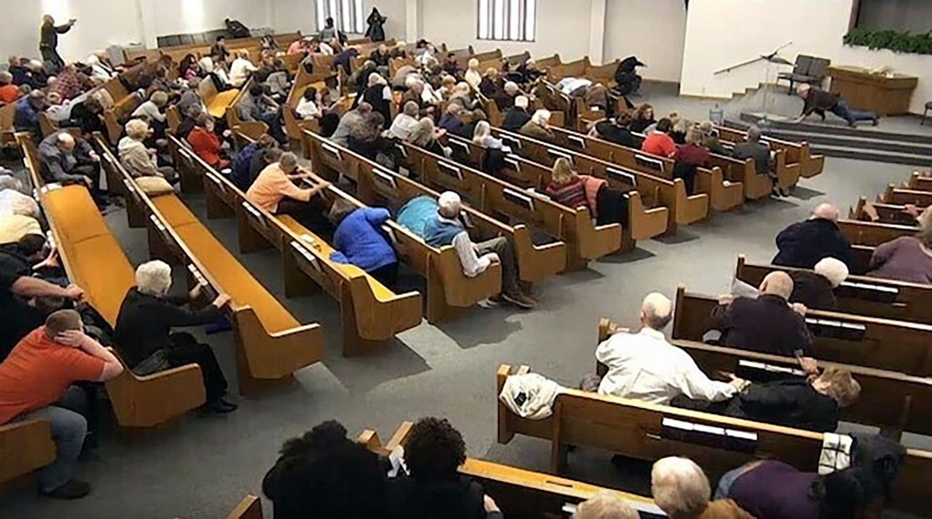 In this still frame from livestreamed video provided by law enforcement, churchgoers take cover while a congregant armed with a handgun, top left, eng...