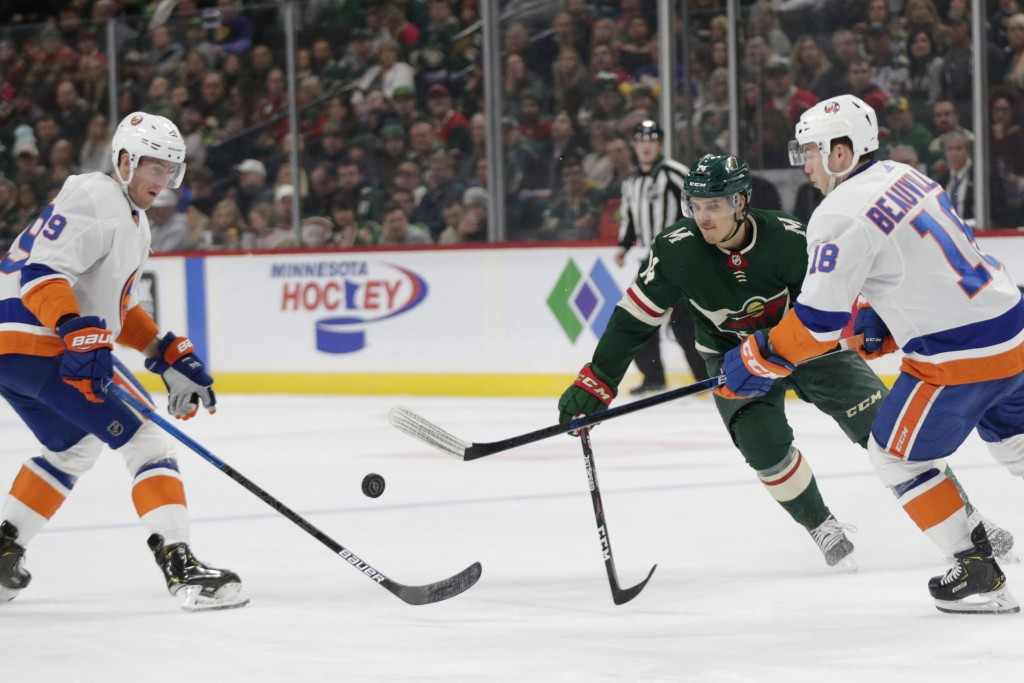 Minnesota Wild center Joel Eriksson Ek (14), New York Islanders center Brock Nelson (29) and Islanders left wing Anthony Beauvillier vie for the puck ...