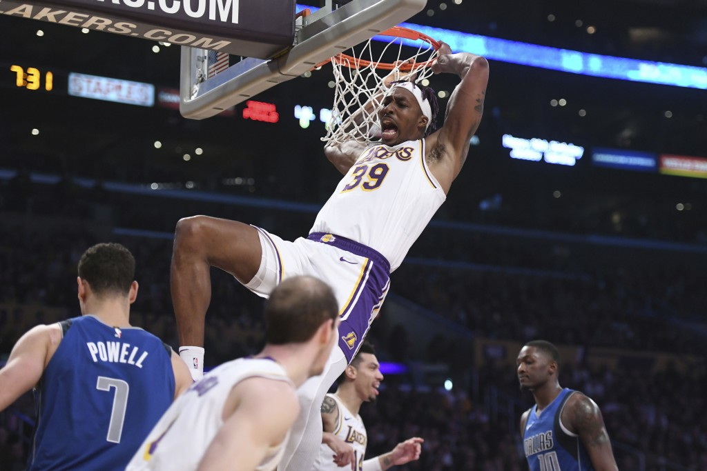 Los Angeles Lakers center Dwight Howard reacts after dunking against the Dallas Mavericks during the first half of an NBA basketball game Sunday, Dec....