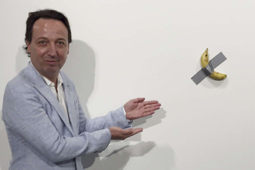 "FILE- In this Dec. 4, 2019 photo, gallery owner Emmanuel Perrotin poses next to Italian artist Maurizio Cattlelan's ""Comedian"" at the Art Basel exhibi..."