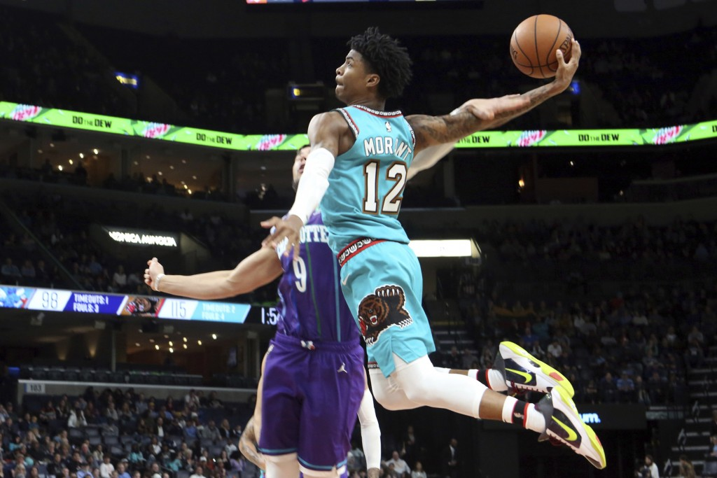 Memphis Grizzlies guard Ja Morant (12) goes up to shoots while defended by Charlotte Hornets center Willie Hernangomez (9) in the second half of an NB...
