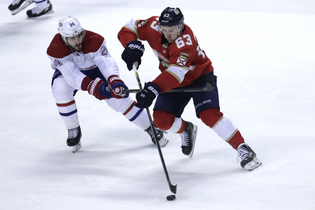 Montreal Canadiens center Phillip Danault (24) and Florida Panthers right wing Evgenii Dadonov (63) fight for the puck during the third period of an N...