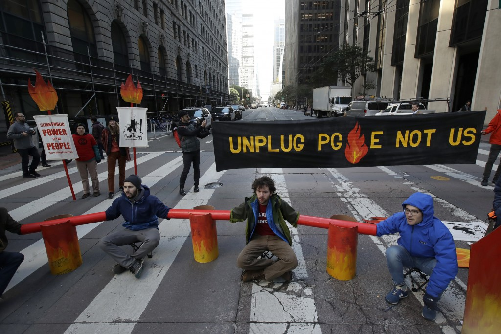 FILE - In this Dec. 16, 2019, file photo, protesters block traffic on Beale Street where a Pacific Gas & Electric building is located in San Francisco...
