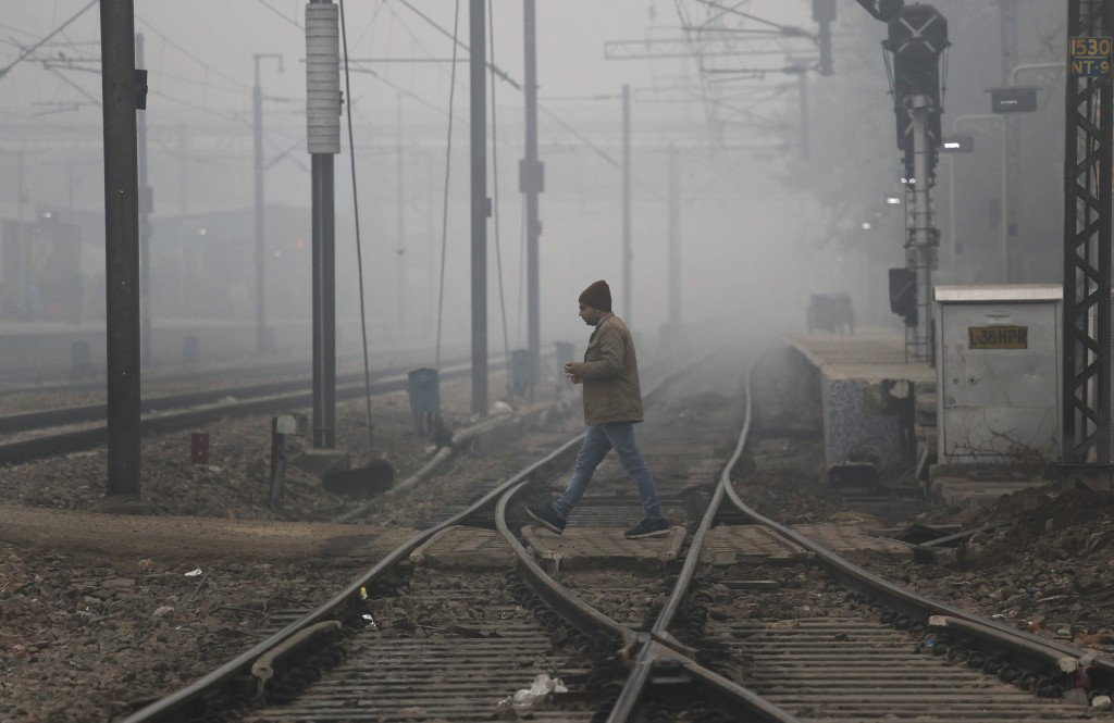 A man crosses railway tracks amidst early morning fog in New Delhi, India, Monday, Dec. 30, 2019. The Indian capital which is witnessing the longest s...