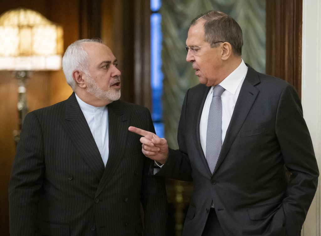 Russian Foreign Minister Sergey Lavrov, right, gestures as he and Iranian Foreign Minister Mohammad Javad Zarif while entering a hall for the talks in...