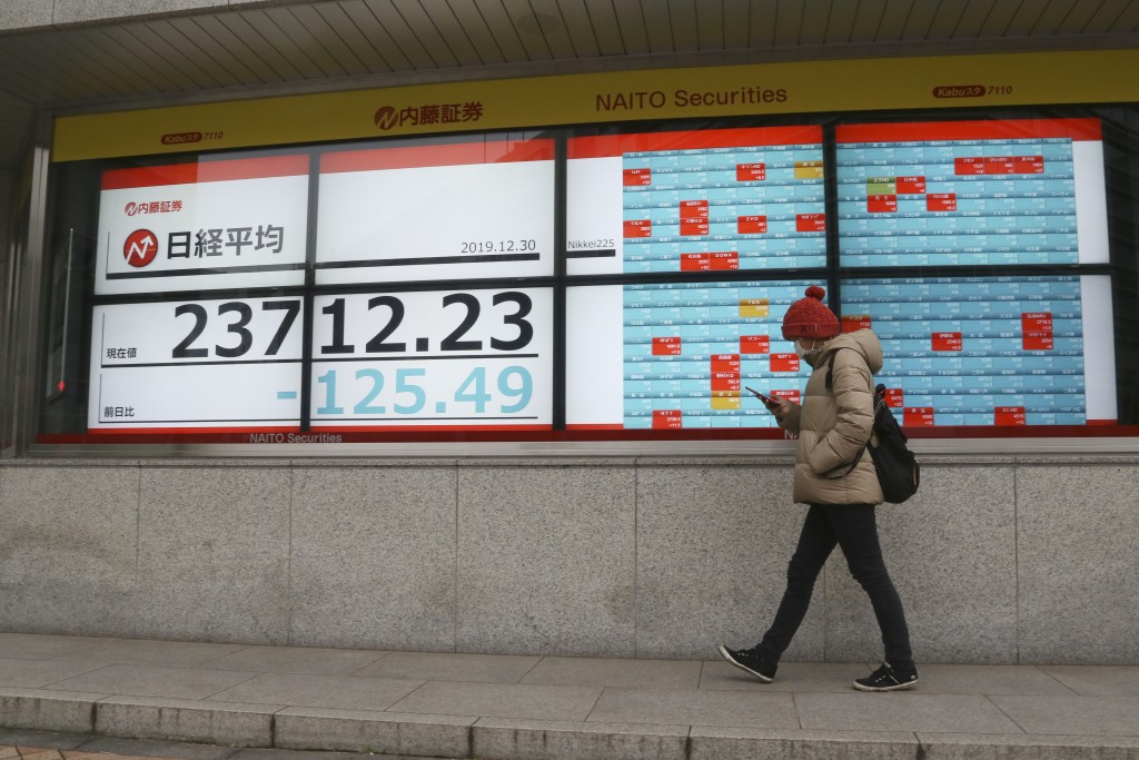 A man walks by an electronic stock board of a securities firm in Tokyo, Monday, Dec. 30, 2019. Asian shares were mostly lower Monday as investors awai...
