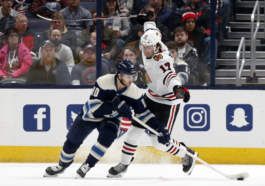 Columbus Blue Jackets forward Alexander Wennberg, left, of Sweden, controls the puck in front of Chicago Blackhawks forward Dylan Strome during the se...