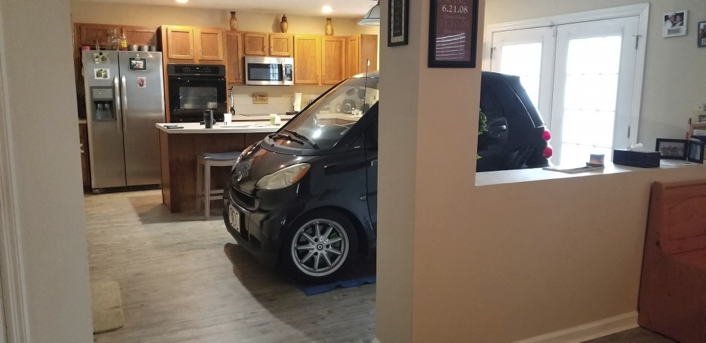 In this Sept. 3, 2019 photo provided by Jessica Eldridge, her husband's Smart car is parked in their kitchen in Jacksonville, Fla. Patrick Eldridge pa...