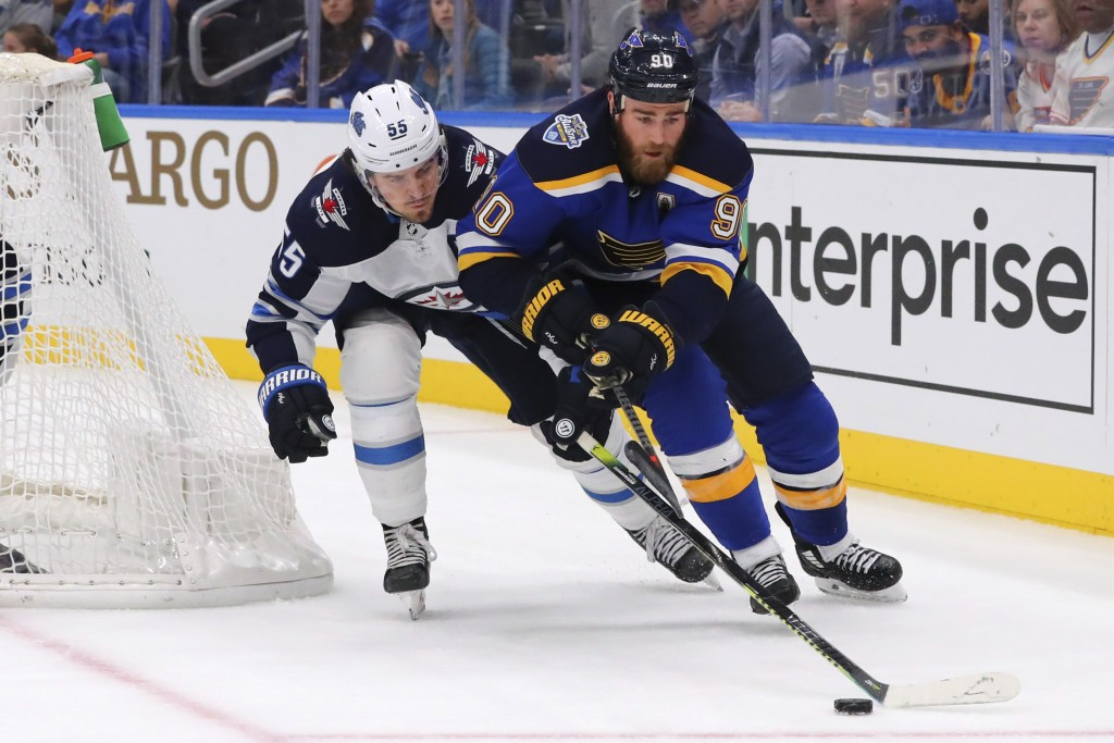 Winnipeg Jets Mark Scheifele (55) pokes the puck away from St. Louis Blues center Ryan O'Reilly (90) during the second period of an NHL hockey game Su...