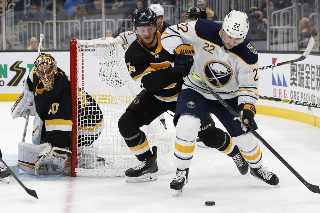 Boston Bruins' Chris Wagner (14) battles Buffalo Sabres' Johan Larsson (22) for the puck during the second period of an NHL hockey game in Boston, Sun...