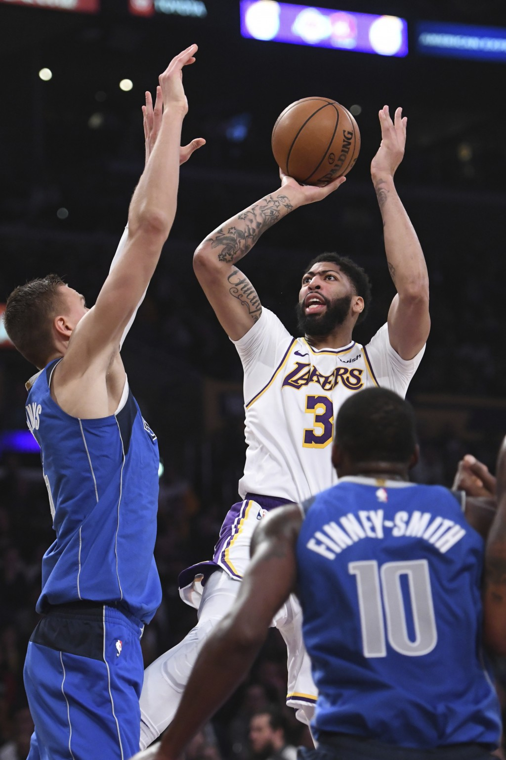 Los Angeles Lakers forward Anthony Davis (3) shoots against the Dallas Mavericks forward Kristaps Porziņgis, left, during the first half of an NBA bas...