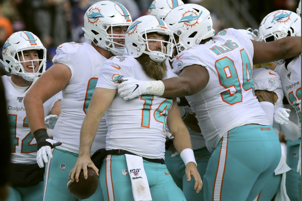 Miami Dolphins quarterback Ryan Fitzpatrick, center, celebrates his touchdown run with teammates in the second half of an NFL football game against th...