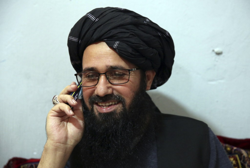In this Saturday, Dec. 14, 2019, photo, Maulvi Niaz Mohammad, 45, talks on his mobile phone during an interview with The Associated Press inside the P...