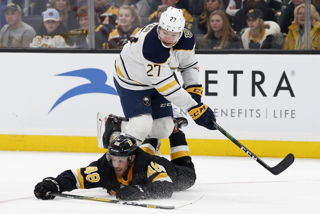 Boston Bruins' Matt Grzelcyk (48) falls while defending against Buffalo Sabres' Curtis Lazar (27) during the second period of an NHL hockey game in Bo...