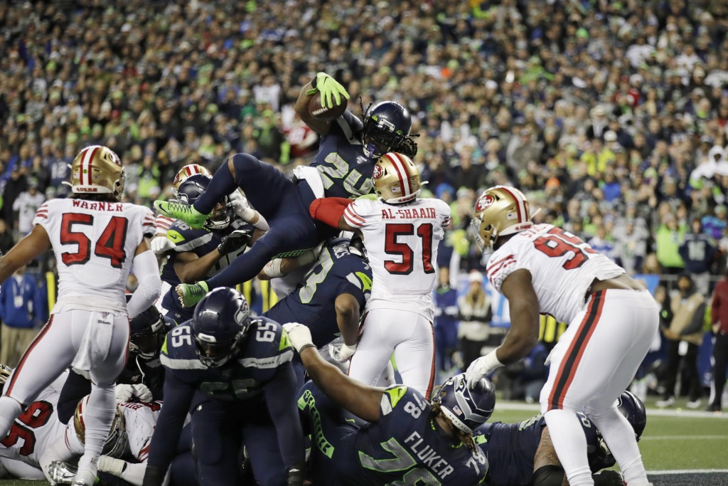 Seattle Seahawks' Marshawn Lynch (24) scores a touchdown on a 1-yard rush against the San Francisco 49ers during the second half of an NFL football ga...
