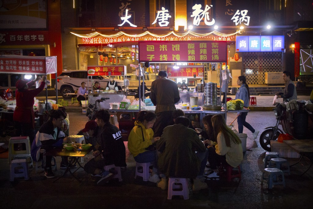 In this March 27, 2019, photo, people eat at an outdoor night market in Xi'an, northwestern China's Shaanxi Province, similar to one at which Yin Hao,...