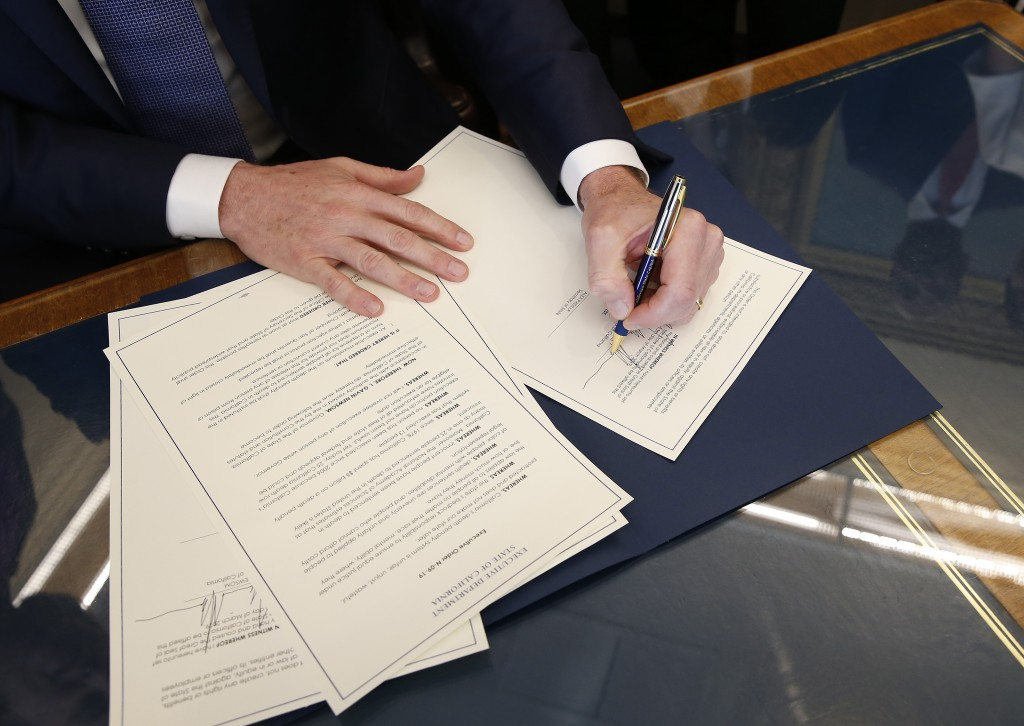 FILE - In this March 13, 2019, file photo, Gov. Gavin Newsom signs the executive order placing a moratorium on the death penalty at his Capitol office...