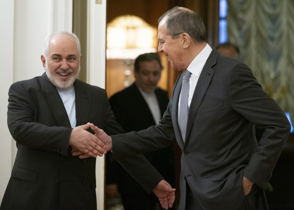 Russian Foreign Minister Sergey Lavrov, and Iranian Foreign Minister Mohammad Javad Zarif shake hands prior to their talks in Moscow, Russia, Monday, ...