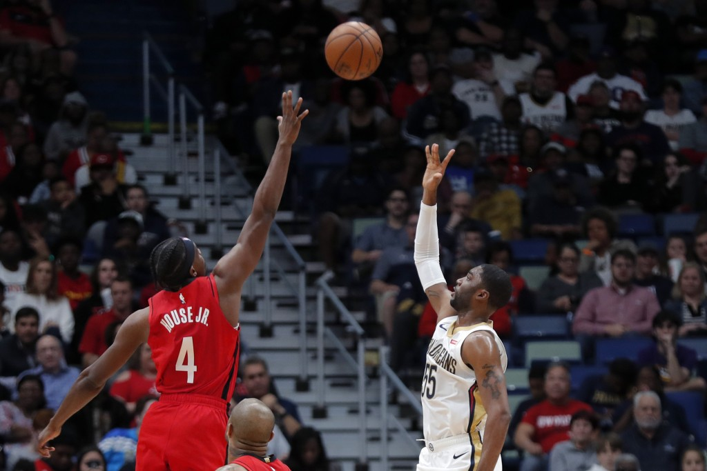 New Orleans Pelicans guard E'Twaun Moore (55) shoots against Houston Rockets forward Danuel House Jr. (4) in the first half of an NBA basketball game ...