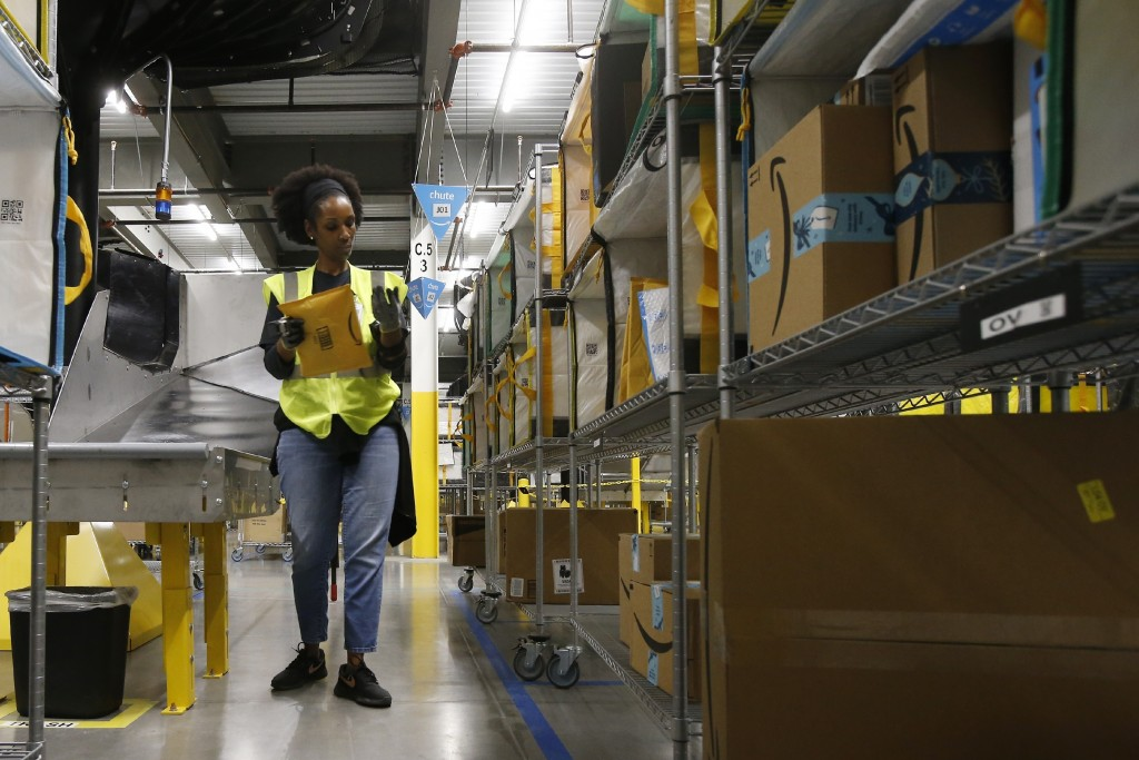 In this Dec. 17, 2019, photo Tahsha Sydnor stows packages into special containers after Amazon robots deliver separated packages by zip code at an Ama...