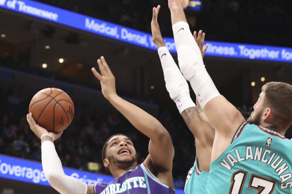Charlotte Hornets forward Miles Bridges, left, goes up to shoot as Memphis Grizzlies center Jonas Valanciunas (17) in the first half of an NBA basketb...