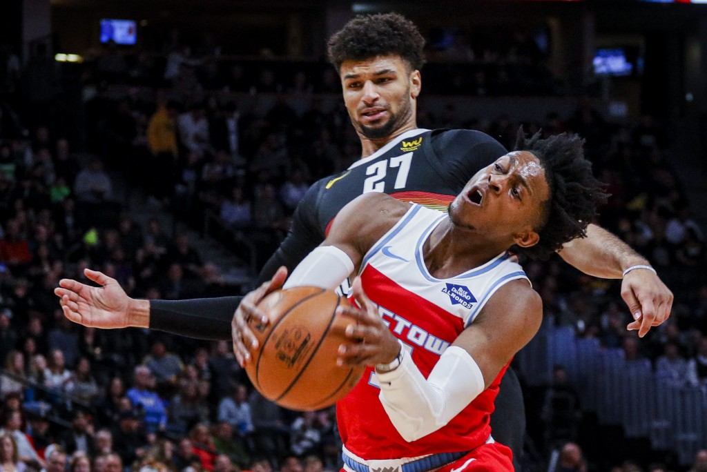 Sacramento Kings guard De'Aaron Fox (5) collides with Denver Nuggets guard Jamal Murray (27) in the first half of an NBA basketball game Sunday, Dec. ...