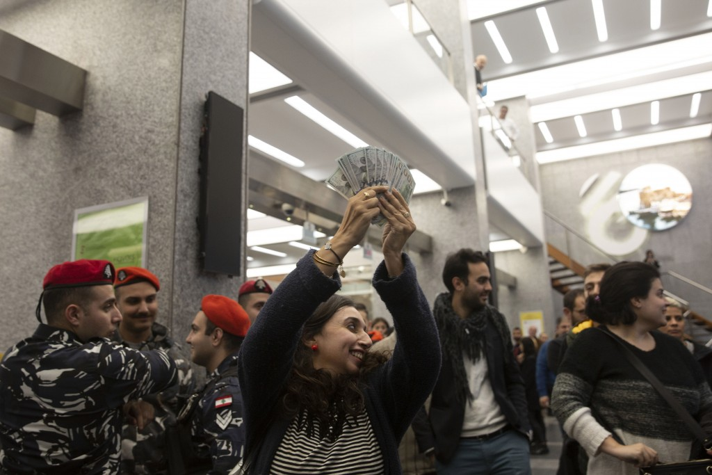 A woman holds up a stack of U.S. dollars she withdrew from a branch of Bank Audi while it was occupied by anti-government protesters on Monday, Dec. 3...