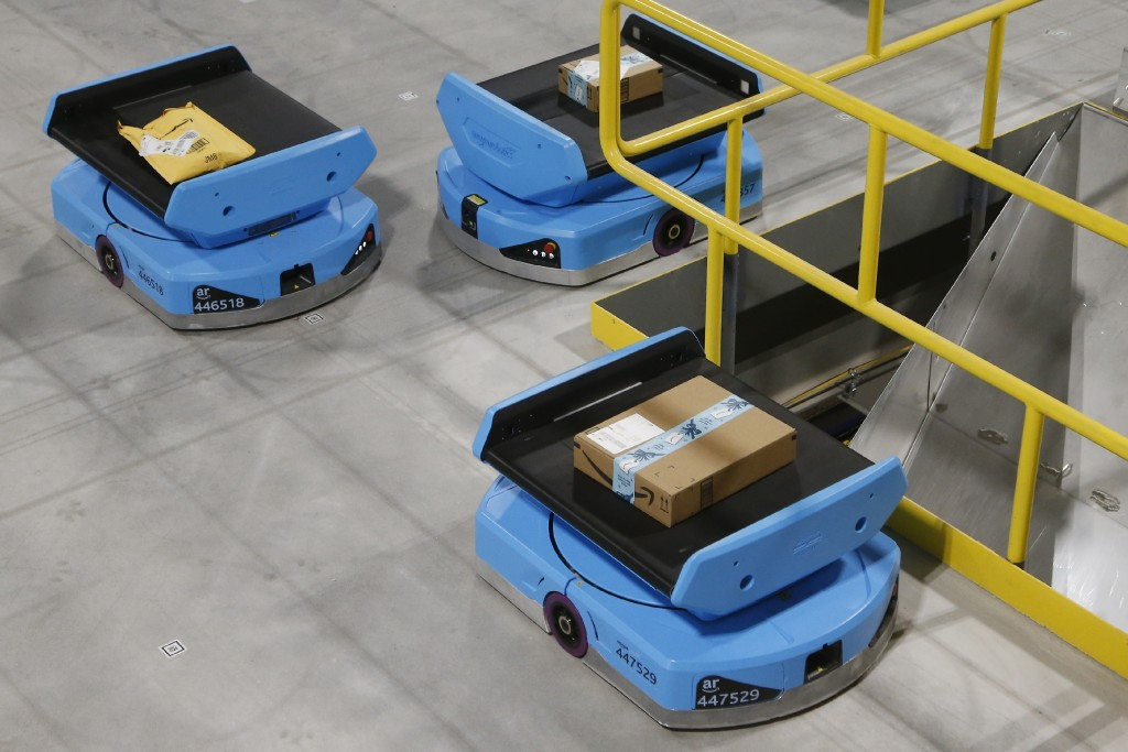 In this Dec. 17, 2019, photo Amazon robots move along the warehouse floor with packages before finding the proper delivery chute, transporting package...