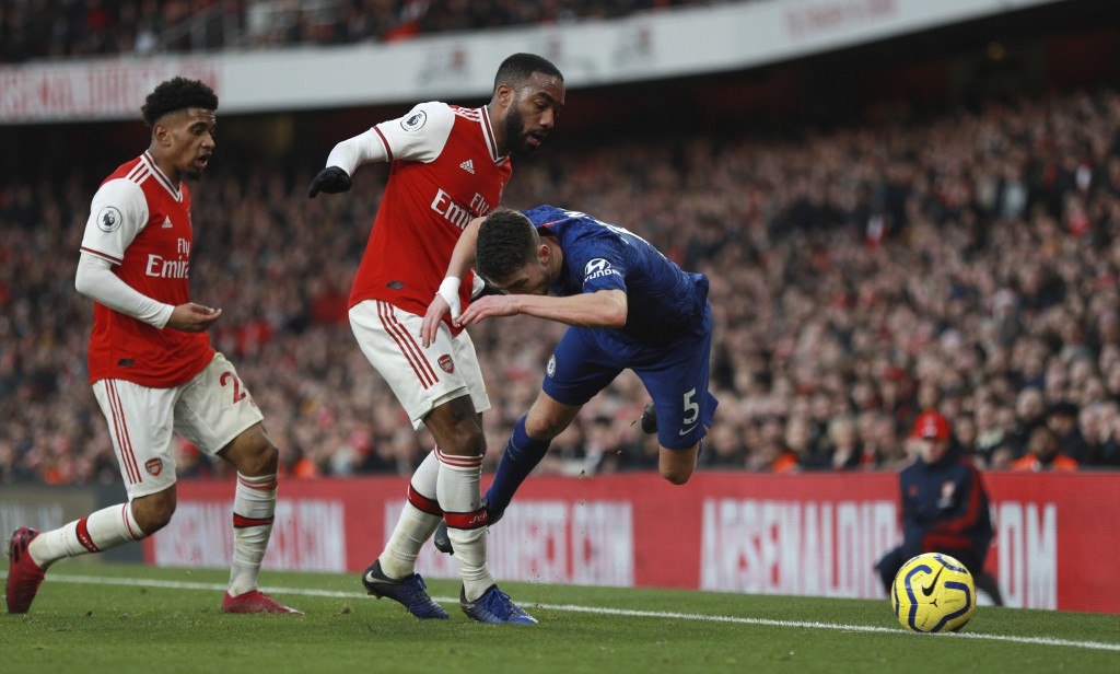 Chelsea's Jorginho, right, is tackled by Arsenal's Alexandre Lacazette during the English Premier League soccer match between Arsenal and Chelsea, at ...