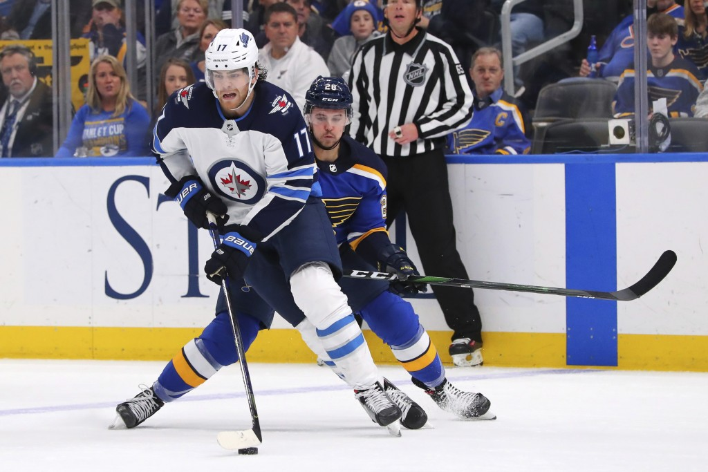 Winnipeg Jets center Adam Lowry (17) controls the puck against St. Louis Blues winger Mackenzie MacEachern (28) during the third period of an NHL hock...