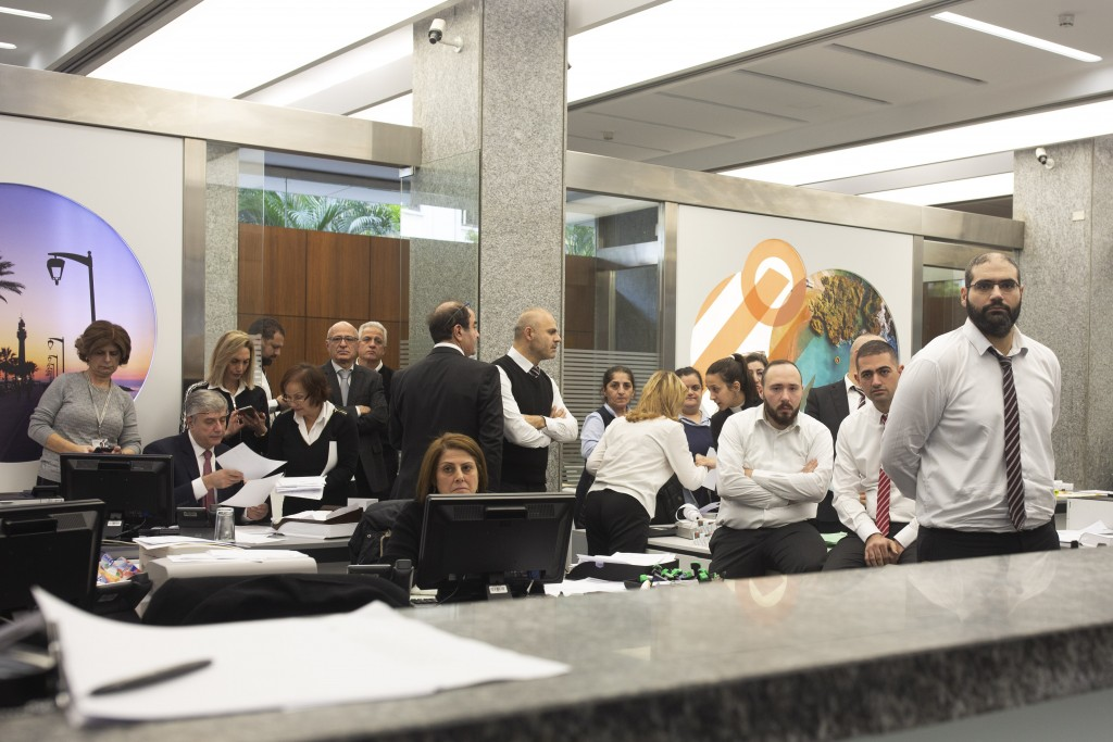 Bank employees watch anti-government protesters shout slogans inside a branch of Bank Audi on Monday, Dec. 30, 2019 in Beirut, Lebanon. (AP Photo/Maya...