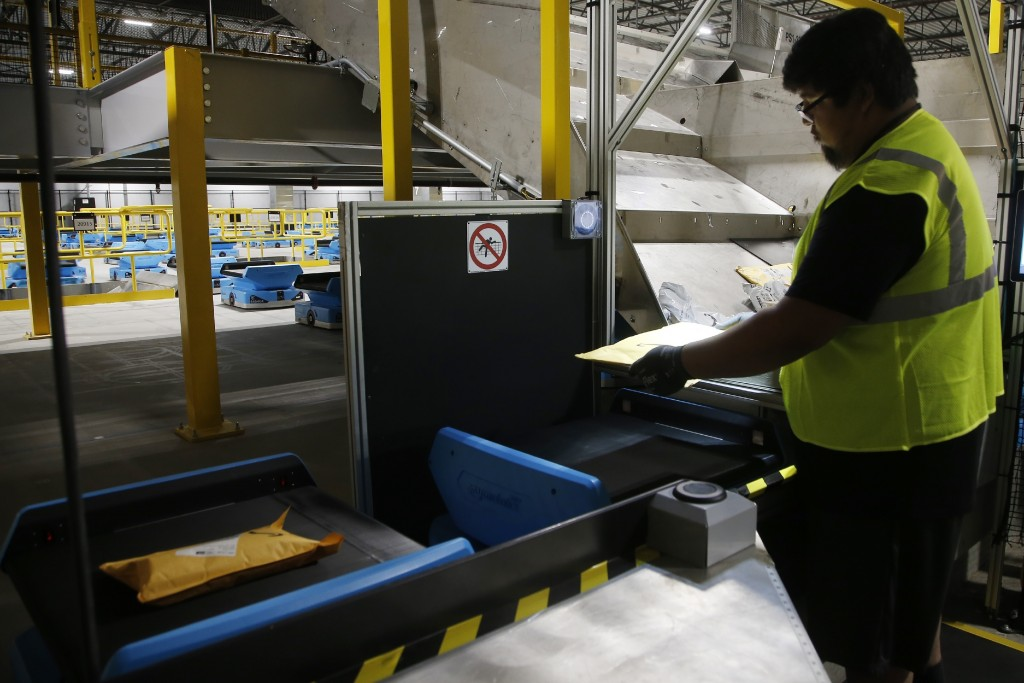 In this Dec. 17, 2019, photo Joseph Salinas places packages onto Amazon robots, transporting packages from workers to chutes that are organized by zip...