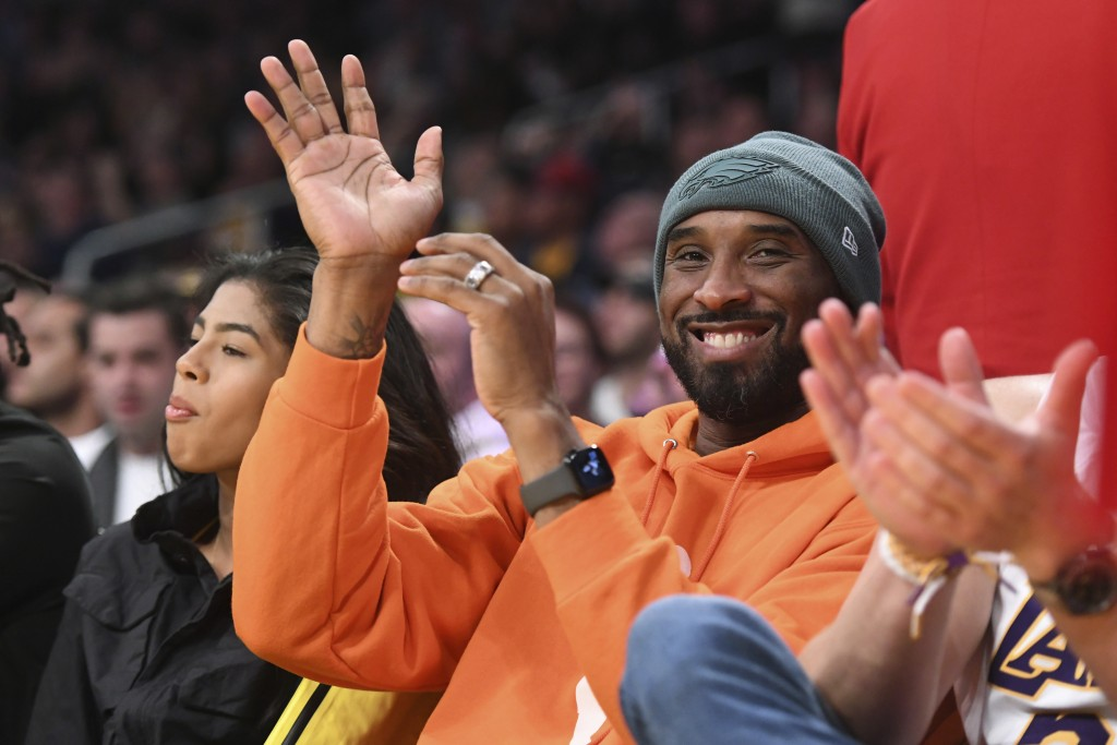 Former Los Angeles Laker Kobe Bryant acknowledges the crowd during the first half of an NBA basketball game against the Dallas Mavericks Sunday, Dec. ...