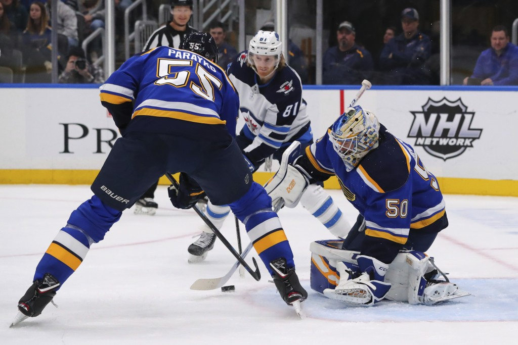 St. Louis Blues goalie Jordan Binnington (50) makes a save against the Winnipeg Jets during the first period of an NHL hockey game Sunday, Dec. 29, 20...