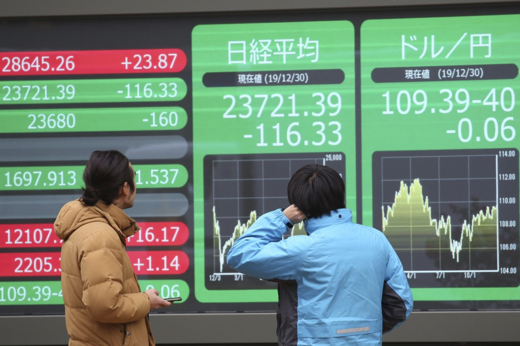 People look at an electronic stock board of a securities firm in Tokyo, Monday, Dec. 30, 2019. Asian shares were mostly lower Monday as investors awai...