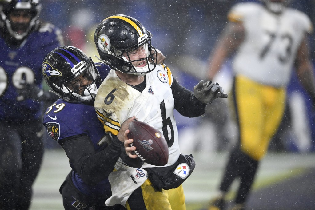 Pittsburgh Steelers quarterback Devlin Hodges (6) tries to throw a pass from his team's end zone as Baltimore Ravens cornerback Brandon Carr (39) grab...