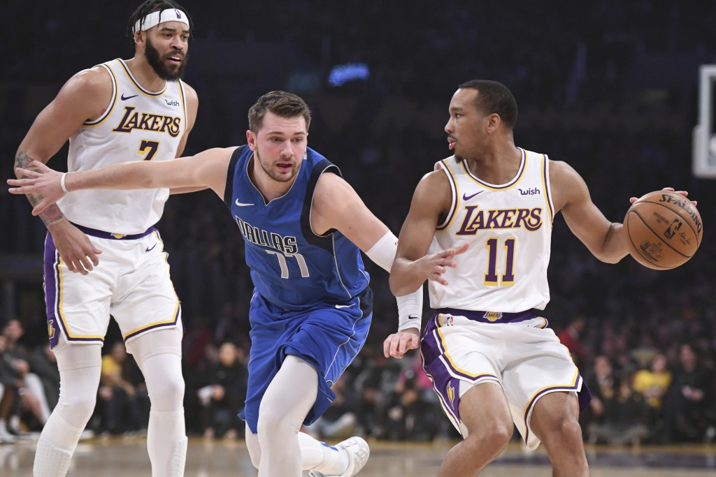 Dallas Mavericks guard Luka Doncic (77) defends Los Angeles Lakers guard Avery Bradley (11) during the first half of an NBA basketball game Sunday, De...