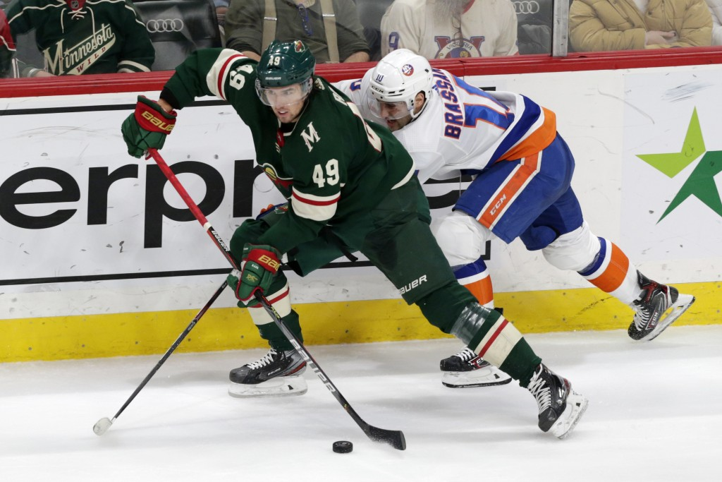 Minnesota Wild center Victor Rask (49) controls the puck in front of New York Islanders center Derick Brassard (10) in the second period of an NHL hoc...