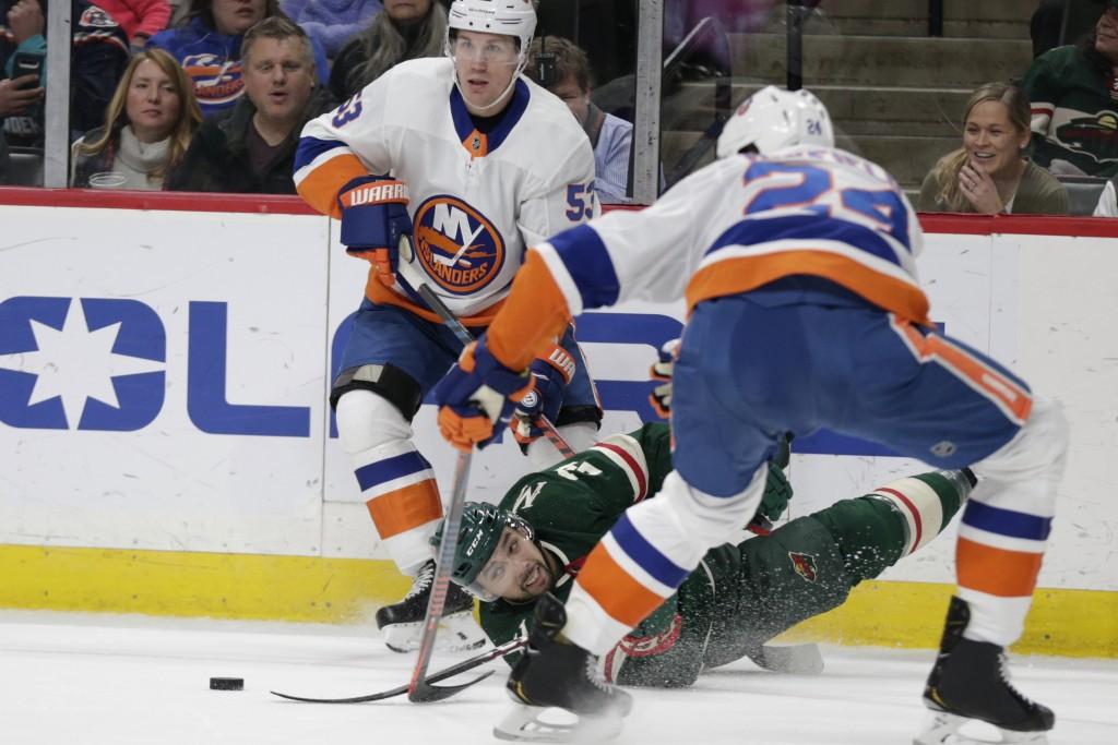Minnesota Wild defenseman Matt Dumba (24) dives for the puck in front of New York Islanders defenseman Scott Mayfield (24) and center Casey Cizikas (5...