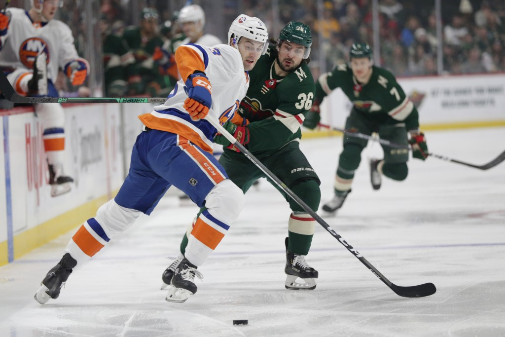 Minnesota Wild right wing Mats Zuccarelllo (36) and New York Islanders defenseman Adam Pelech (3) battle for the puck in the first period of an NHL ho...