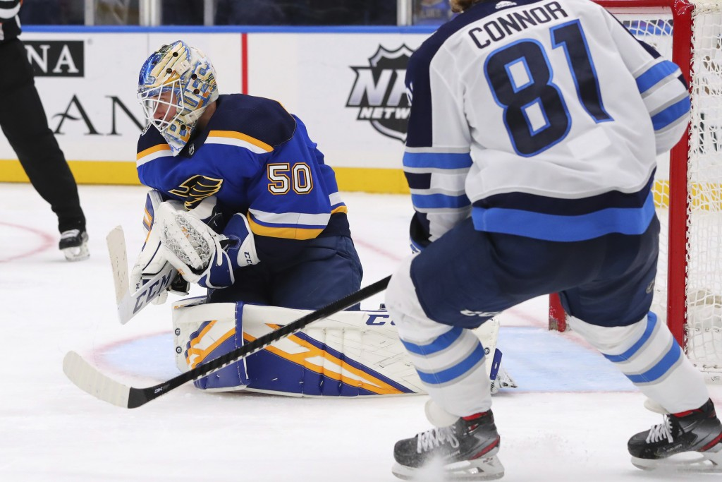 St. Louis Blues goalie Jordan Binnington (50) makes a save against the Winnipeg Jets during the third period of an NHL hockey game Sunday, Dec. 29, 20...