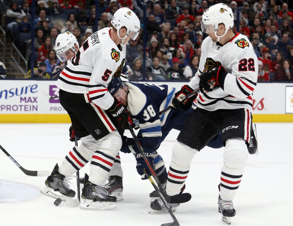 Columbus Blue Jackets forward Boone Jenner, center, collides with Chicago Blackhawks defenseman Connor Murphy, left, as Blackhawks forward Ryan Carpen...