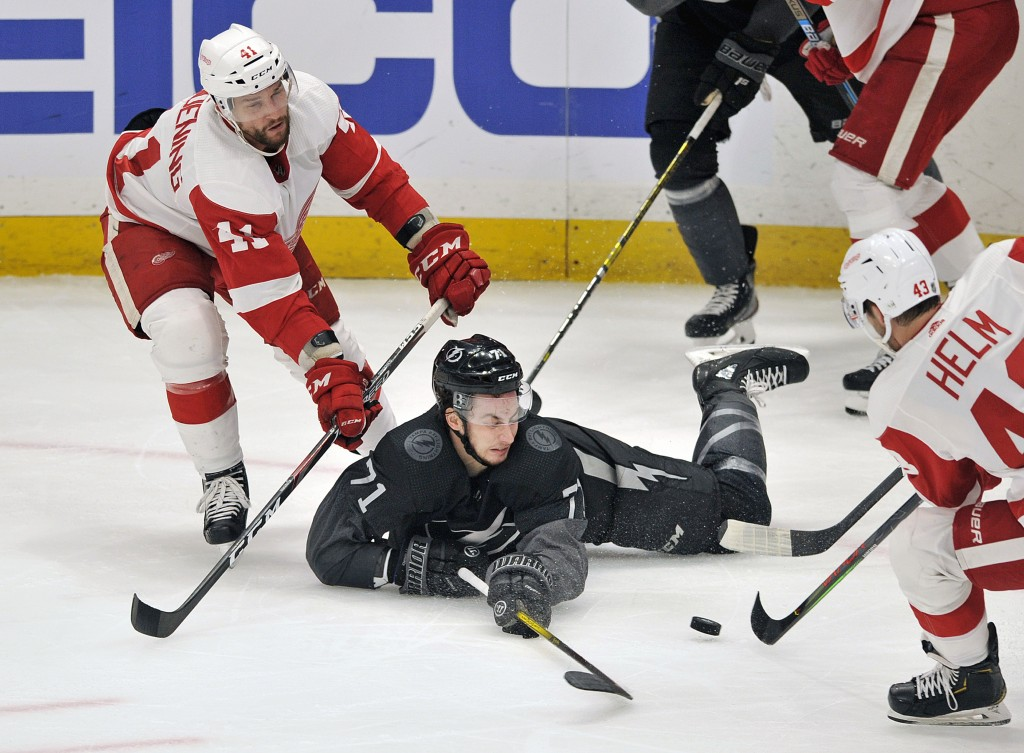 Tampa Bay Lightning center Anthony Cirelli (71) hits the ice between Detroit Red Wings' Luke Glendening (41) and Darren Helm (43) during the second pe...