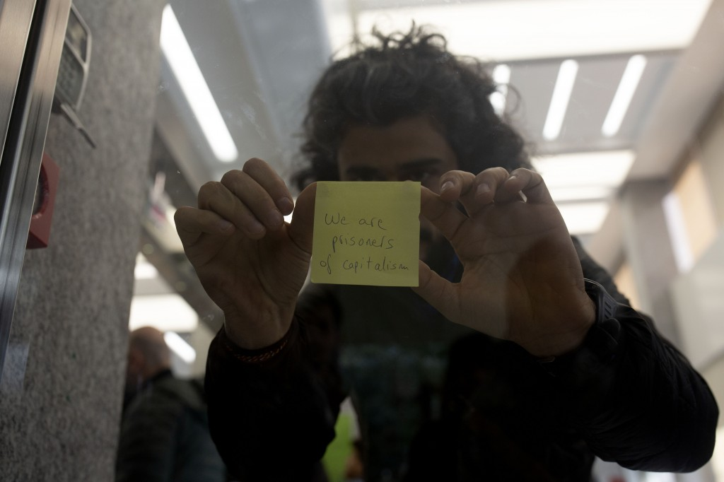 An anti-government protester tapes a message to the window of a branch of Bank Audi while protesters and customers were briefly locked inside on Monda...