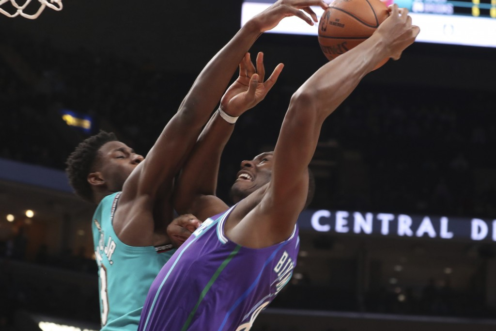 Memphis Grizzlies forward Jaren Jackson Jr., left, defends against Charlotte Hornets center Bismack Biyombo (8) in the first half of an NBA basketball...