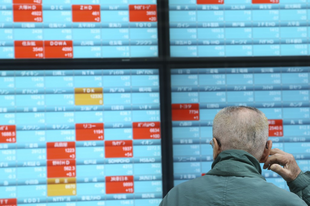 A man looks at an electronic stock board of a securities firm in Tokyo, Monday, Dec. 30, 2019. Asian shares were mostly lower Monday as investors awai...